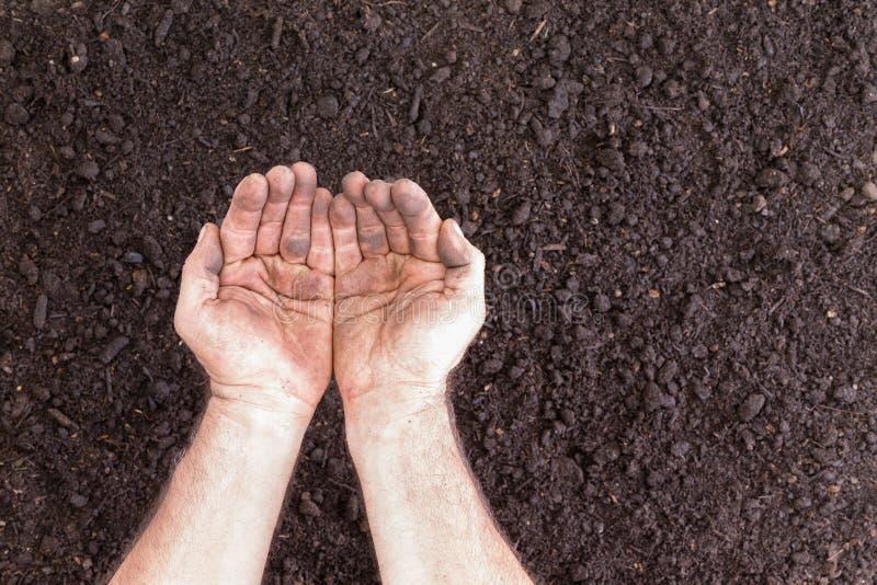 举行在光秃的土壤的对空的手 图库摄影