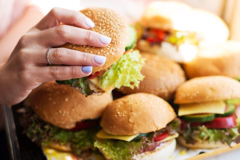 举行在女性手便当汉堡,美国不健康的卡路里的少女在背景的膳食 免版税库存照片