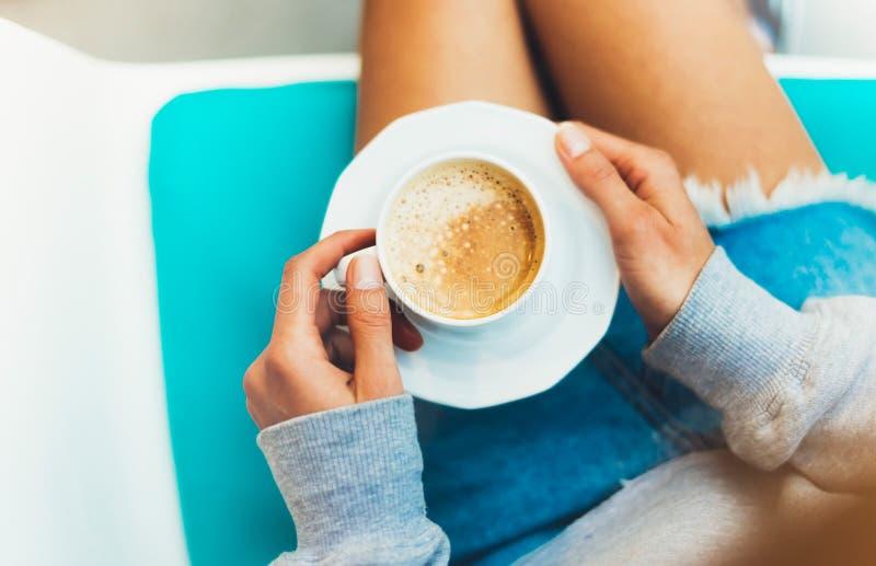 举行在女性手和饮料热的芳香咖啡上的少妇在早餐时间的cuppuccino,行家m的旅客女孩 库存照片