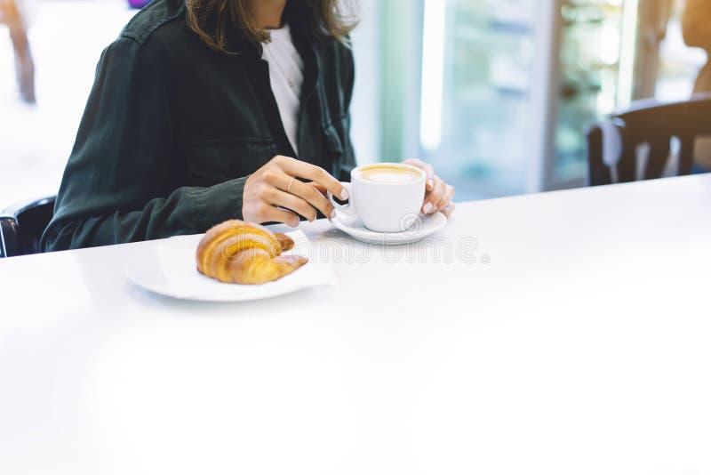 举行在女性手新月形面包和饮料热的芳香咖啡或者茶在早餐时间,行家旅客微笑女孩的少妇 库存图片