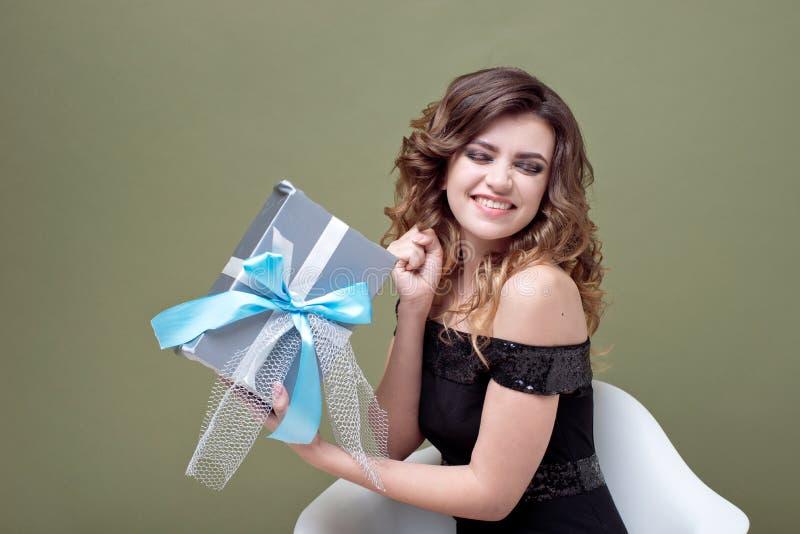 举行在她的头上的乐趣妇女镶边了有在绿色背景隔绝的丝带的当前箱子 对广告 ST 库存照片