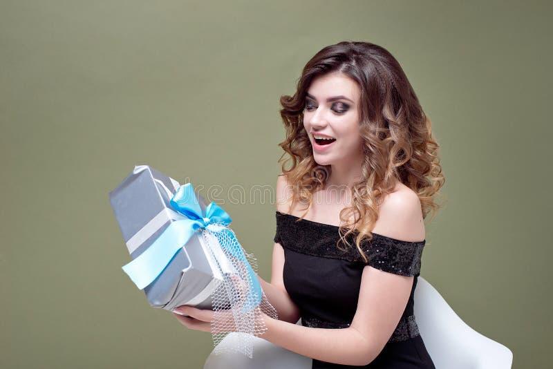 举行在她的头上的乐趣妇女镶边了有在绿色背景隔绝的丝带的当前箱子 对广告 ST 免版税库存照片