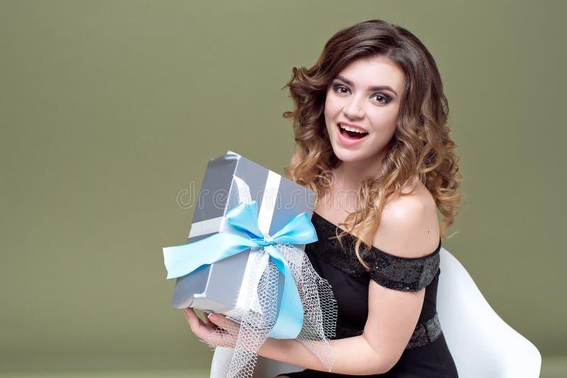 举行在她的头上的乐趣妇女镶边了有在绿色背景隔绝的丝带的当前箱子 对广告 ST 免版税库存图片