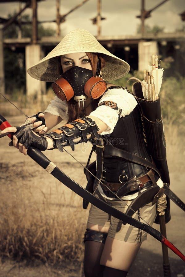 举行在她的手上的面具的可爱的妇女战士鞠躬  免版税库存图片