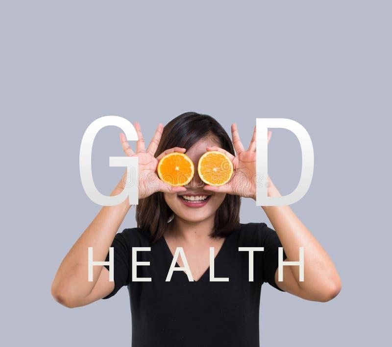 举行在她的眼睛前面的橙色在灰色背景的年轻亚裔妇女画象切片和微笑 愉快的妇女,健康 免版税图库摄影