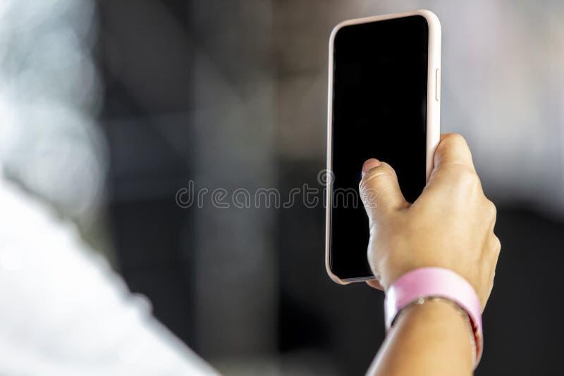 举行在手机的妇女手有被弄脏的背景 免版税库存图片