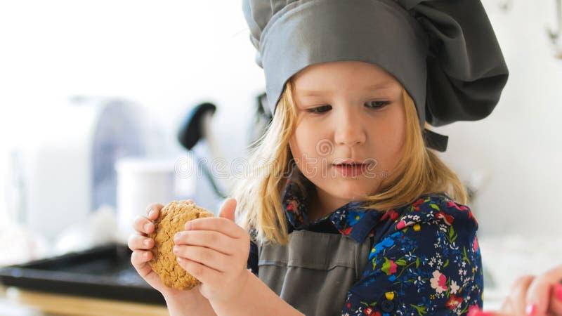 举行在手自创曲奇饼的小女孩面包师 免版税图库摄影