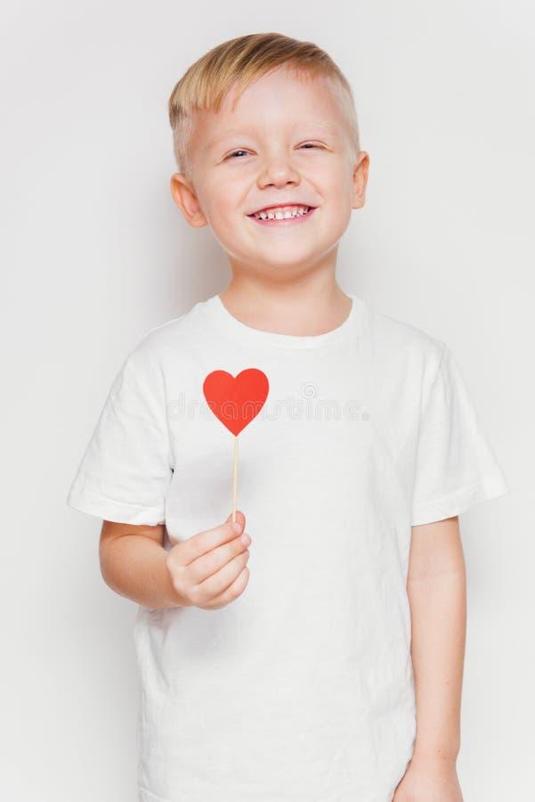 举行在棍子的年轻白肤金发的男孩心脏形状 免版税图库摄影