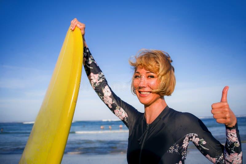 举行在热带海滩的年轻性感的美丽和愉快的冲浪者妇女黄色水橇板微笑的快乐的享用的暑假 库存照片