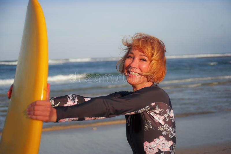 举行在热带海滩w的年轻性感的美丽和愉快的冲浪者女孩黄色水橇板微笑的快乐的享用的暑假 免版税库存照片