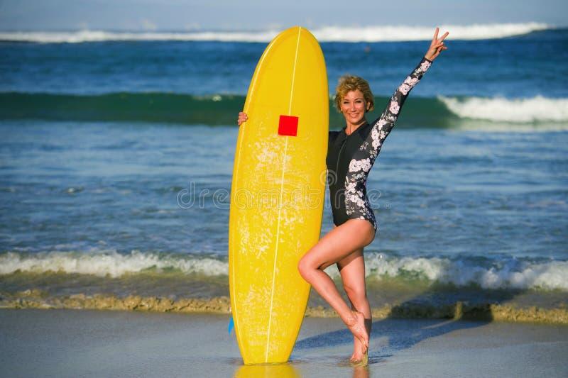 举行在热带海滩w的年轻性感的美丽和愉快的冲浪者女孩黄色水橇板微笑的快乐的享用的暑假 免版税库存图片