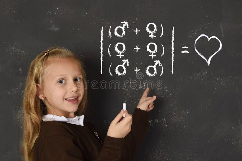 举行在黑板的制服的女小学生白垩文字站立为性别取向自由  免版税库存图片