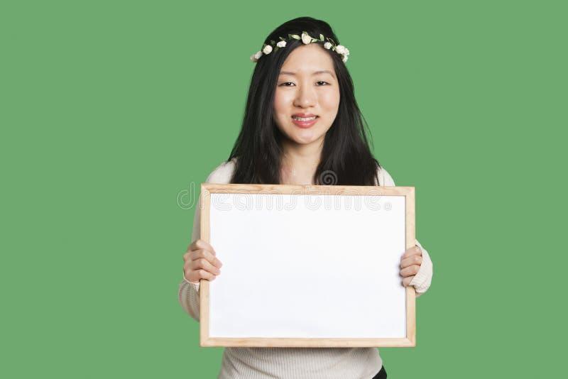 举行在绿色背景的一个少妇的画象一空白的whiteboard 免版税库存照片