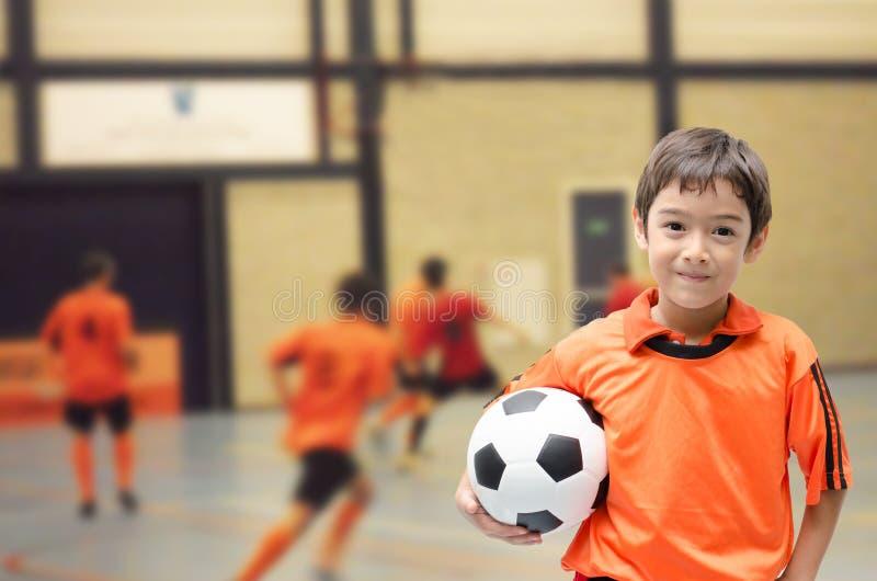 举行在futsal健身房的小男孩橄榄球 免版税库存图片