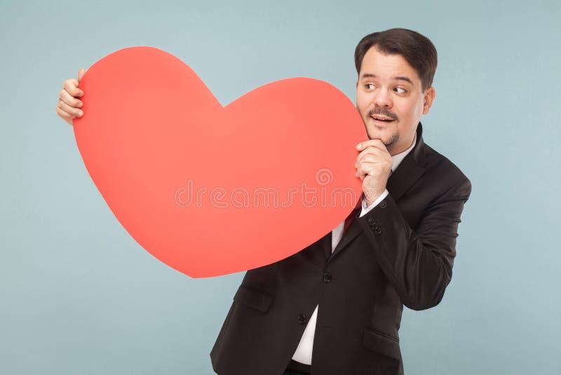 举行大红色心脏和微笑的幸福成人商人 库存照片