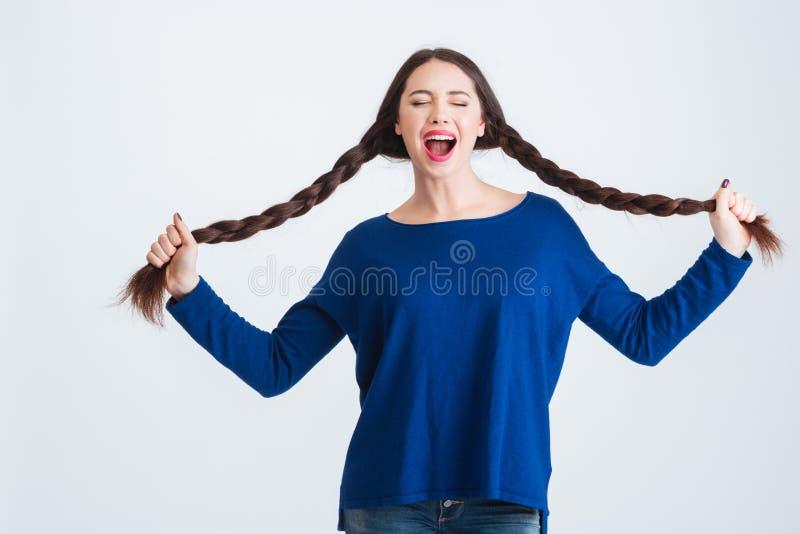 举行她两长辫子和呼喊的可笑的俏丽的妇女 免版税库存照片