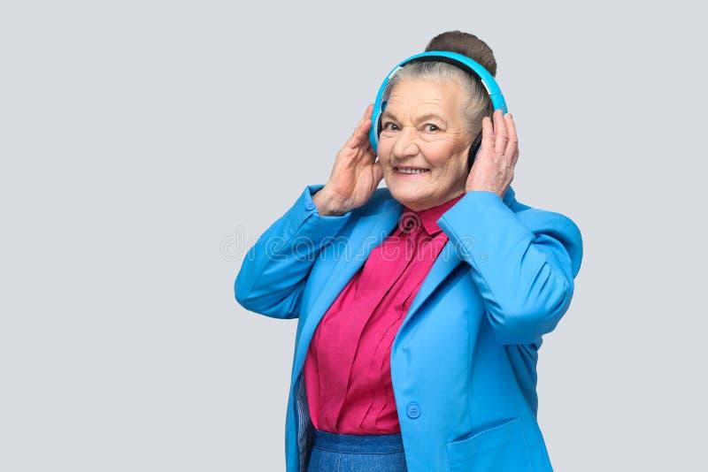 举行她的bl的五颜六色的便装样式的时髦愉快的祖母 免版税库存照片