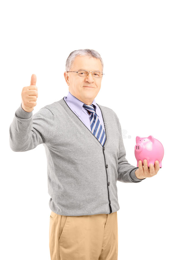 举行存钱罐和给的微笑的成熟绅士拇指u 免版税库存图片