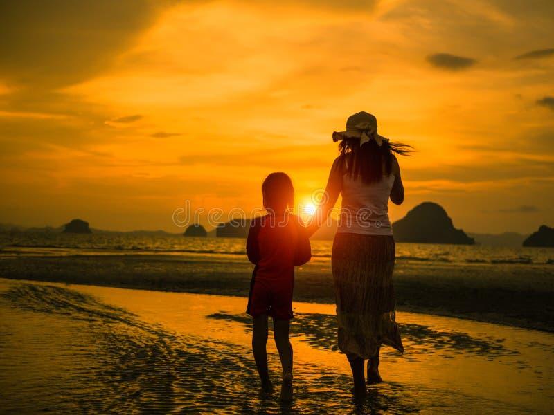 举行孩子手和步行在海滩的母亲剪影在日落期间 免版税库存照片