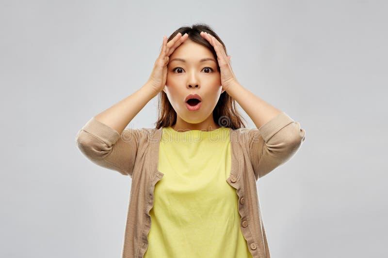 举行对她的头的震惊亚裔妇女 库存图片