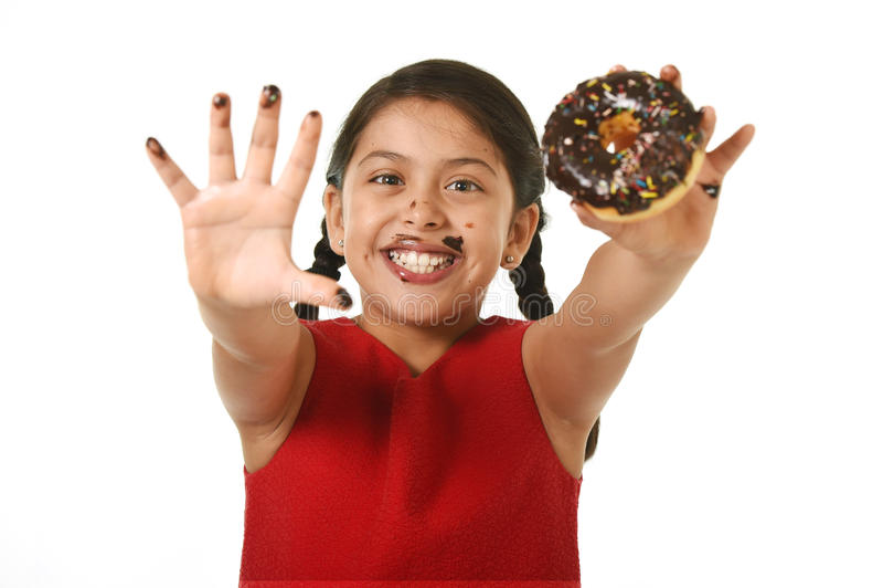 举行巧克力多福饼用手和嘴被弄脏和肮脏显示的微笑的红色礼服的拉丁女孩愉快 库存图片