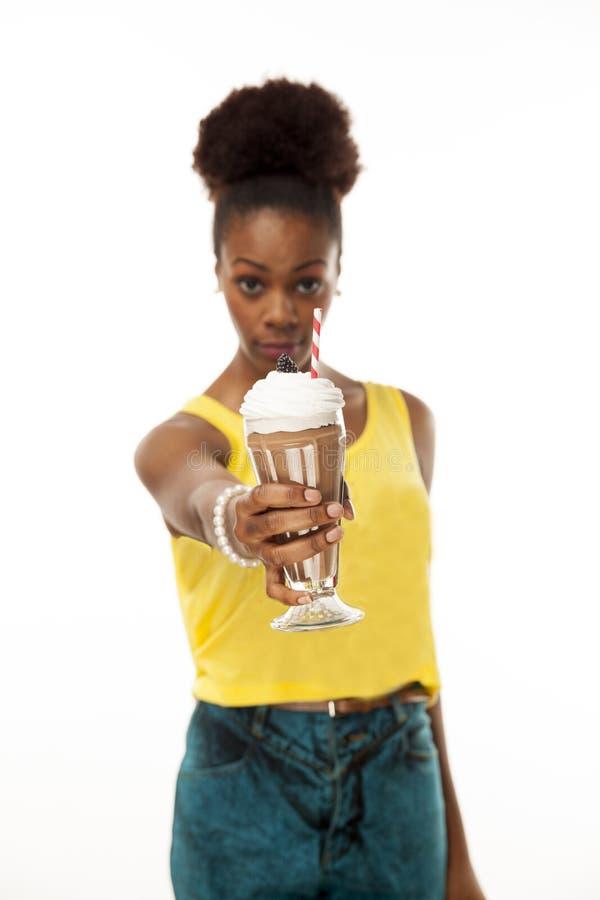举行巧克力牛奶冰淇淋的非裔美国人的妇女 免版税库存照片