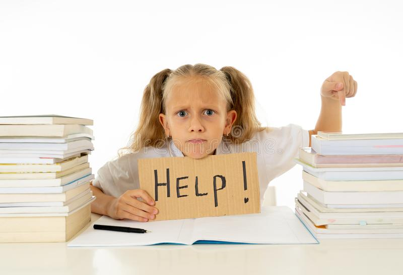 举行帮助的哀伤的疲乏和恼怒的白肤金发的学校女孩签字在做家庭作业和学习与书的重音对于儿童教育 免版税库存照片