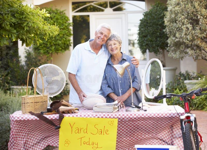举行庭院旧货出售的资深夫妇 库存照片