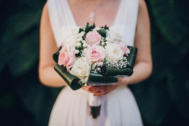 举行异常的婚姻的花束关闭的丝绸礼服的时髦的新娘在夏天公园 新娘婚姻的花束结构的绿色 图库摄影