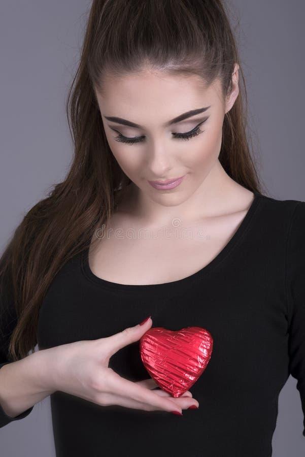 举行心脏形状的妇女反对她的身体 库存图片