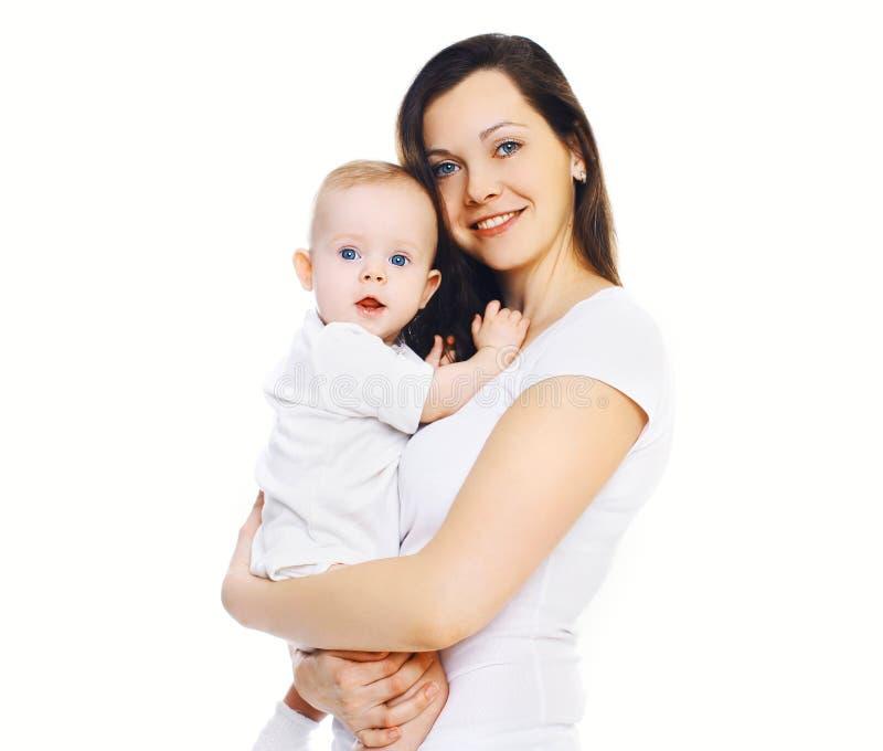 举行愉快的年轻的母亲画象递她的婴孩 免版税图库摄影