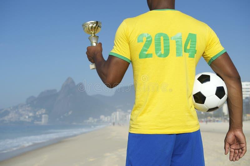 举行战利品和橄榄球的冠军巴西足球运动员 免版税图库摄影