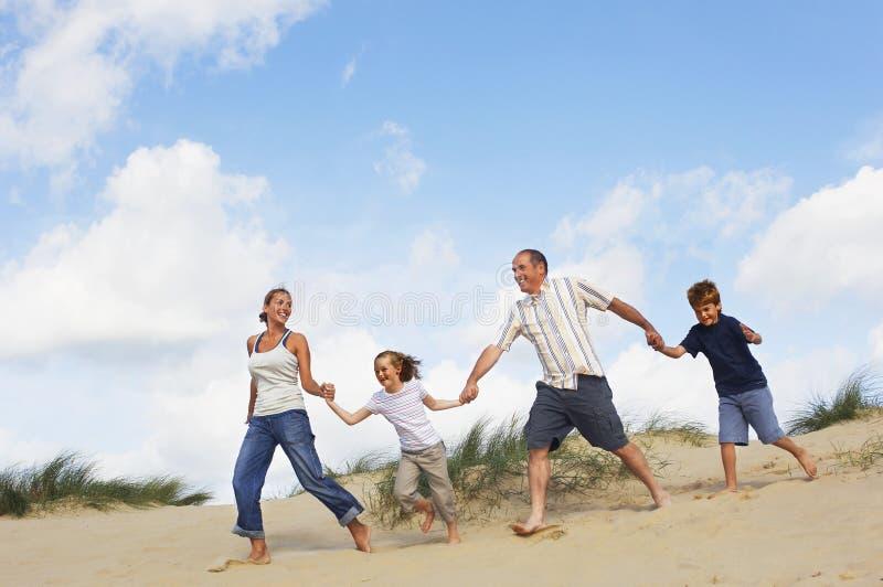 举行手和赛跑在沙子的家庭 免版税库存照片