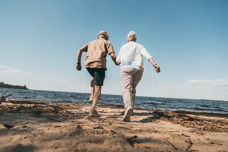 举行手和赛跑在沙滩的资深夫妇 免版税库存照片