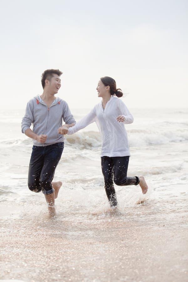 举行手和赛跑的年轻夫妇由水在海滩,中国渐近 库存照片