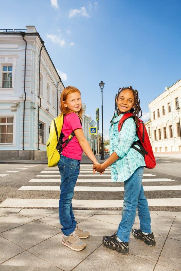 举行手和身分的两个女孩在路附近 免版税图库摄影