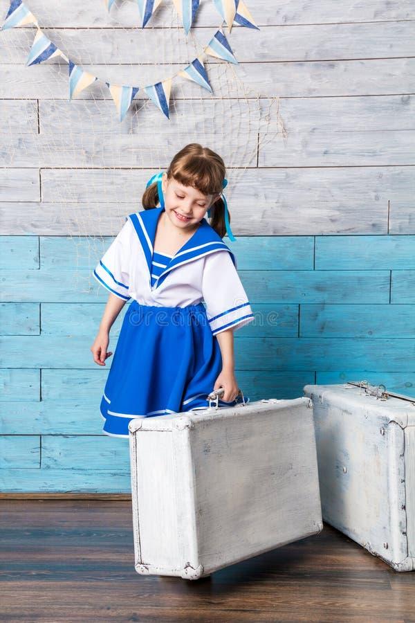 举行手提箱和笑的小女孩 库存图片