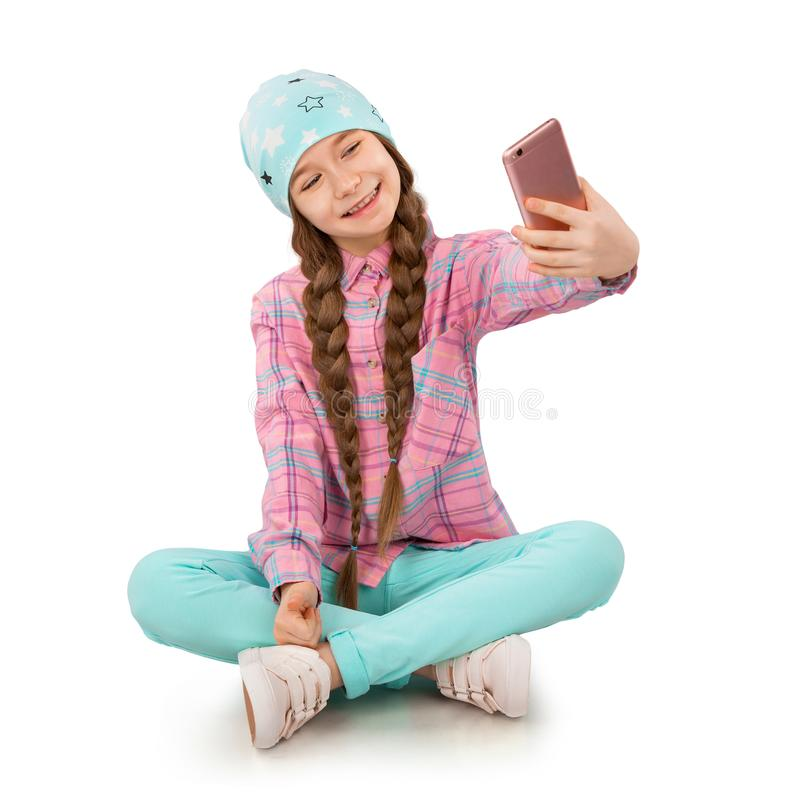举行手机和做selfie在白色背景的微笑的小女孩 库存图片