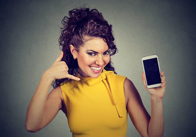 举行手机陈列的俏丽的妇女告诉我手势 库存图片