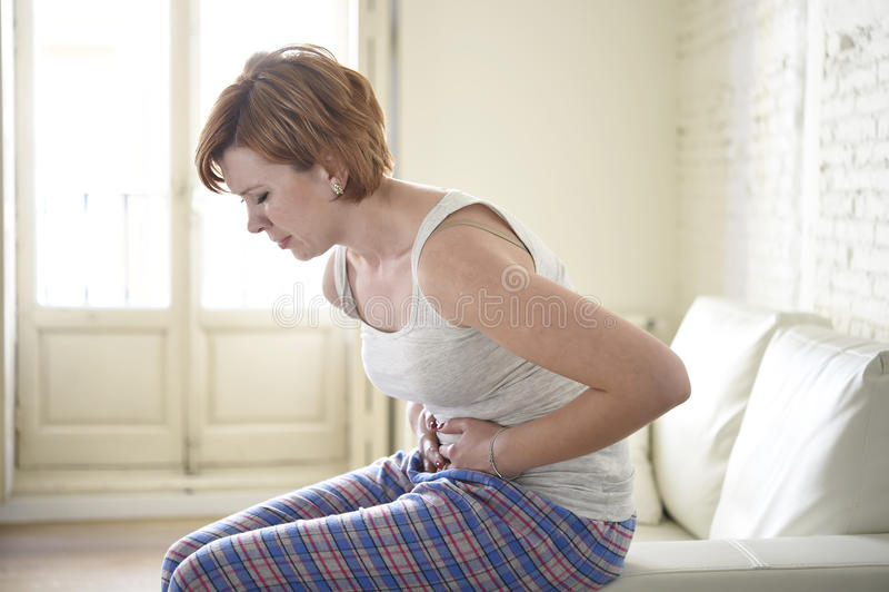 举行损害的沙发长沙发的女孩腹部遭受的胃痉挛和期间痛苦 免版税库存照片