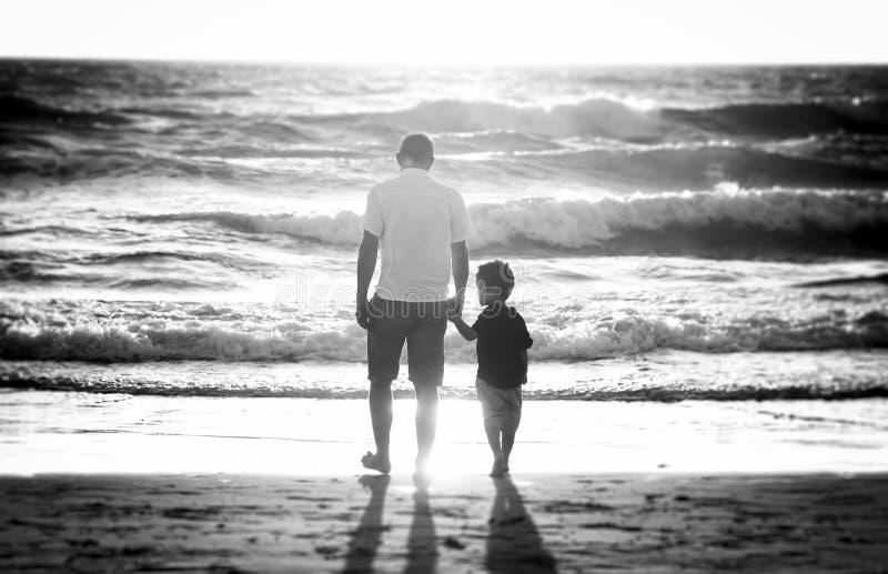 举行握的愉快的父亲一起走在与赤足的海滩的小儿子的手 图库摄影