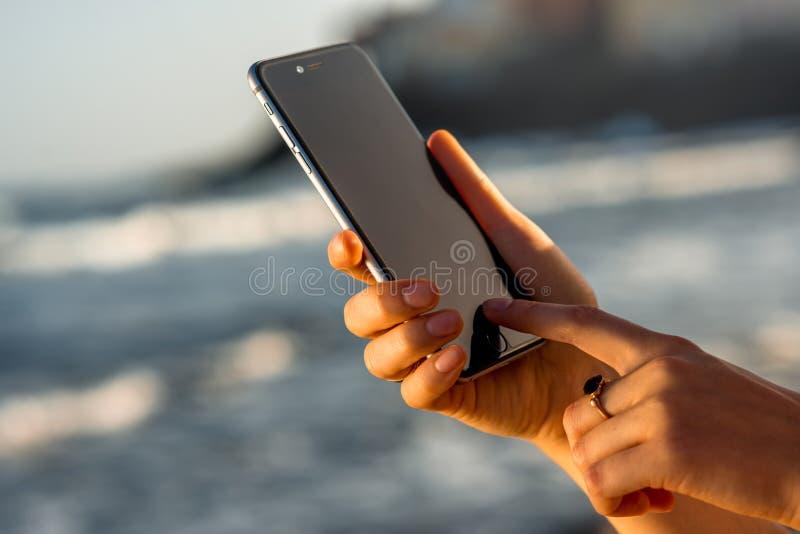 举行新的iPhone 6s的女性手间隔灰色 免版税库存图片