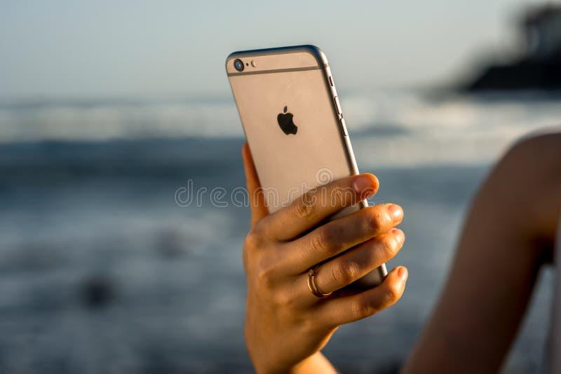 举行新的iPhone 6s的女性手间隔灰色 免版税库存照片