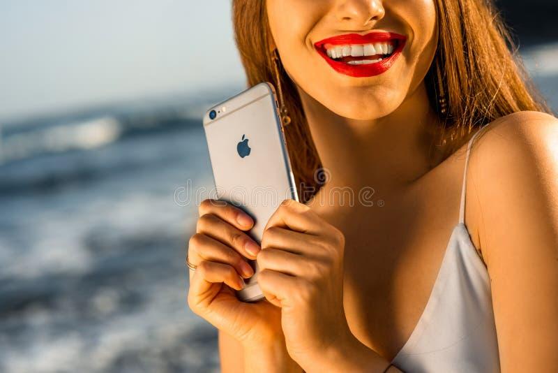 举行新的iPhone 6s的妇女 免版税图库摄影