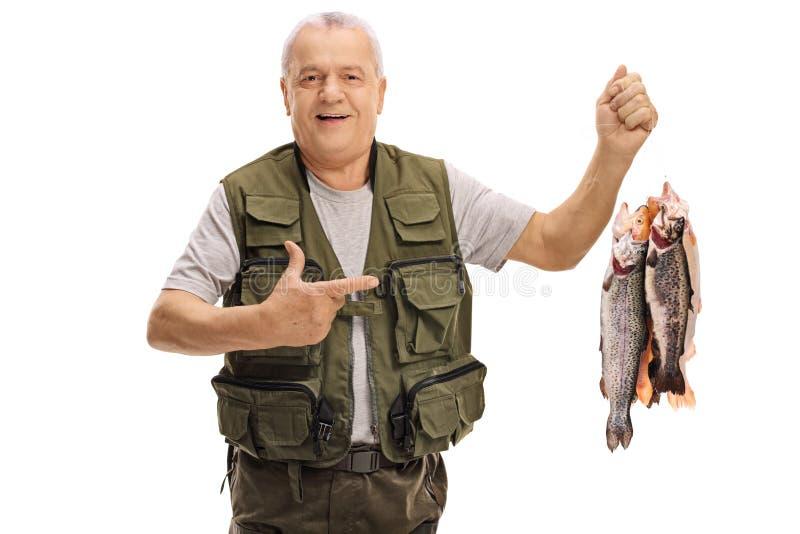 举行新近地被抓的鱼和指向的快乐的成熟渔夫 免版税库存照片