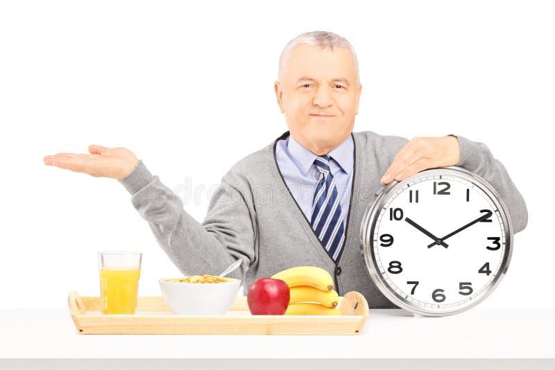 举行时钟和打手势的资深绅士 免版税库存图片