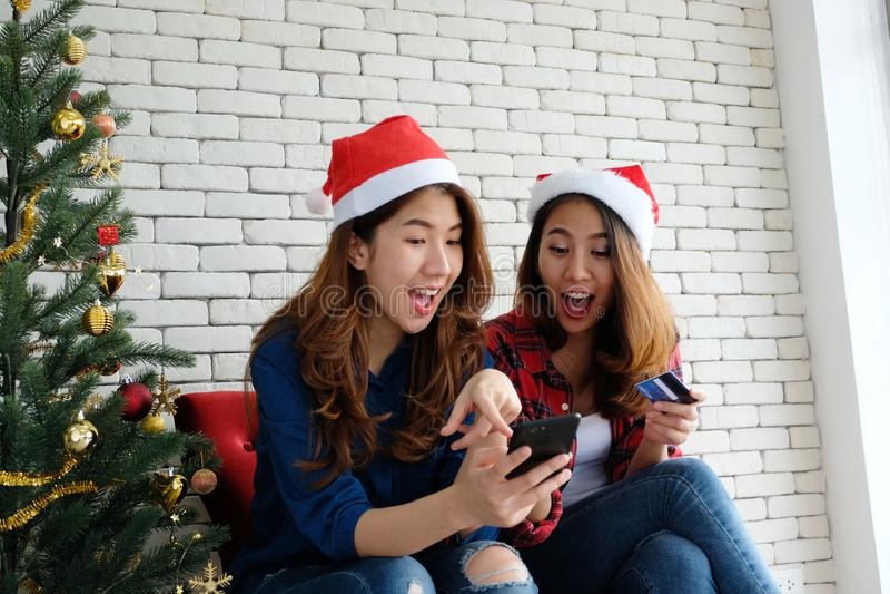举行智能手机和信用卡whi的两名年轻逗人喜爱的亚洲妇女 免版税库存图片