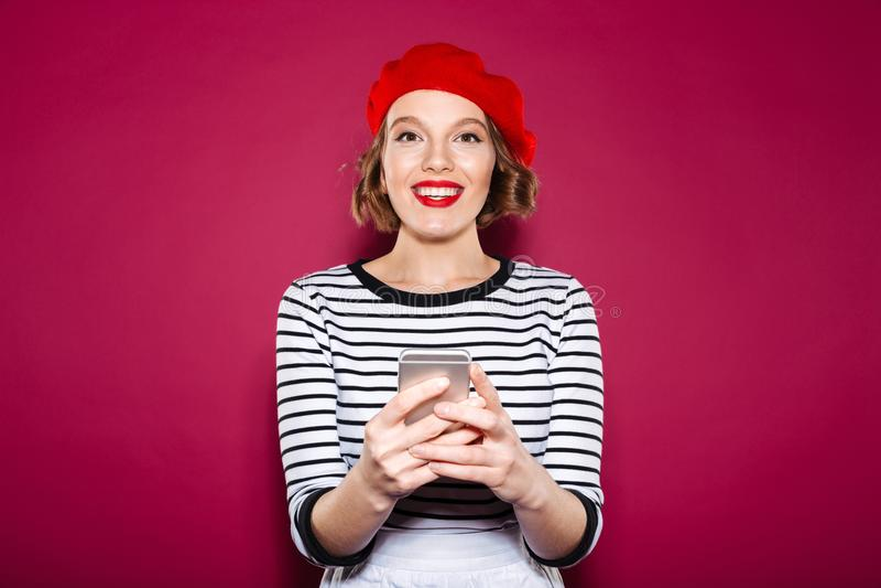 举行智能手机和看的微笑的姜妇女照相机 免版税库存照片