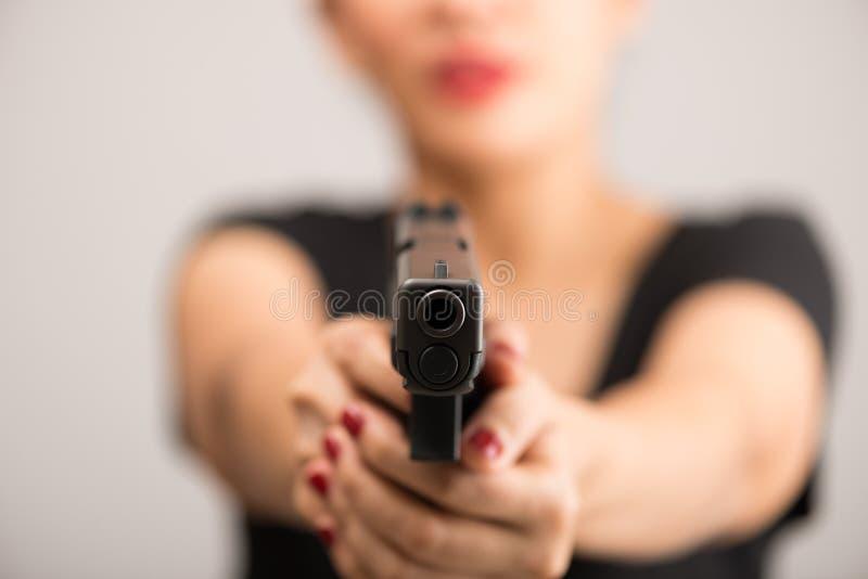 举行枪瞄准的少妇亚裔女孩 免版税库存图片