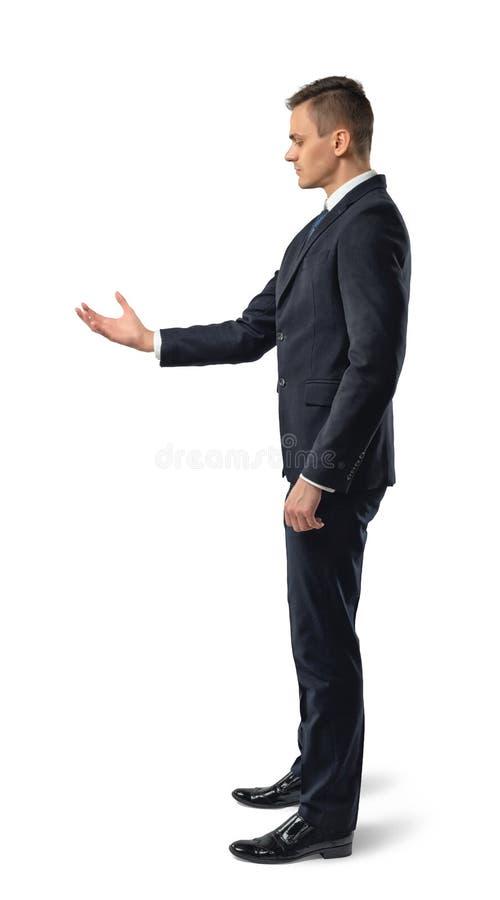 举行某事在他的手上的商人侧视图,隔绝在白色背景 免版税库存照片